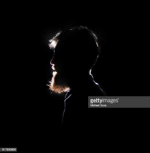 silhouette of bearded man smiling - tegenlicht stockfoto's en -beelden
