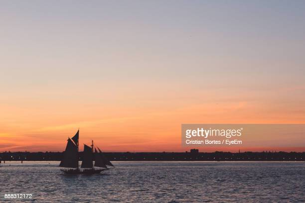 Silhouette Of Boat In Sea During Sunset
