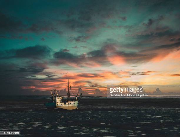 Silhouette Of Boats In Sea Against Cloudy Sky