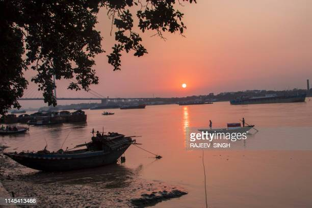 silhouette of boats sailing over river ganges in kolkata during sunset - ganges river stock pictures, royalty-free photos & images