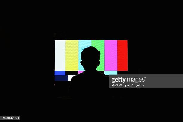 silhouette of boy in front of television screen - kanaal stockfoto's en -beelden