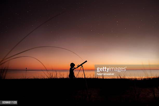 silhouette of boy looking at stars through telescope - curiosity stock photos and pictures