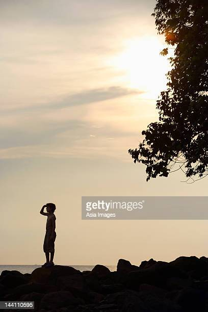 Silhouette of boy looking out to sea