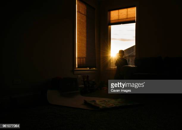 silhouette of boy looking through window at home - darkroom stock pictures, royalty-free photos & images