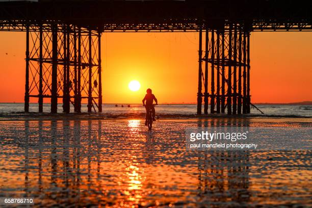 silhouette of boy on brighton brach at sunset - low tide stock pictures, royalty-free photos & images