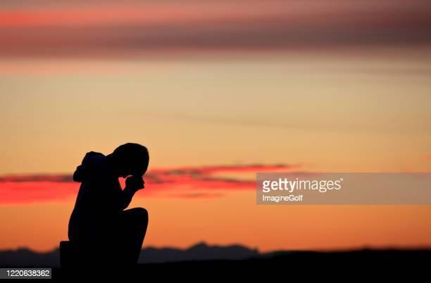 silhouette des jungen beten - religion stock-fotos und bilder