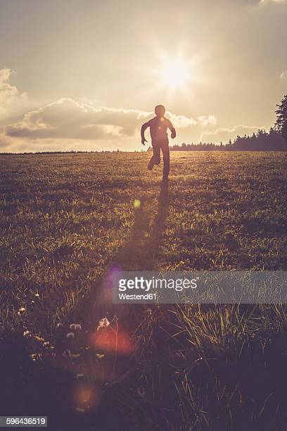 Silhouette of boy running on a meadow at backlight