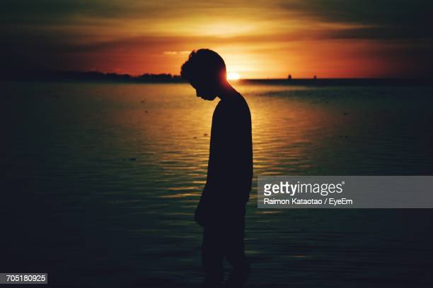 Silhouette Of Boy Standing On Beach At Sunset