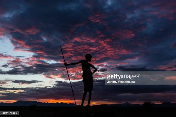 Silhouette of boy with walking stick under sunset sky, Nyangaton, Ethiopia