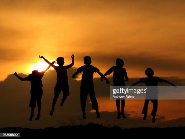 silhouette of boys jumping, pekanbaru, riau, indonesia - riau images - fotografias e filmes do acervo