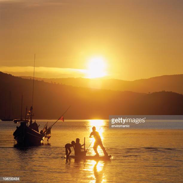 Silhouette of Boys Playing on Raft in Water at Sunset