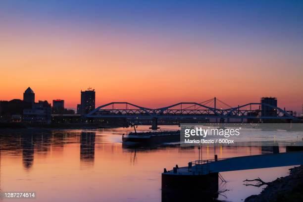 silhouette of bridge over river against sky during sunset,mannheim,germany - mannheim stock-fotos und bilder