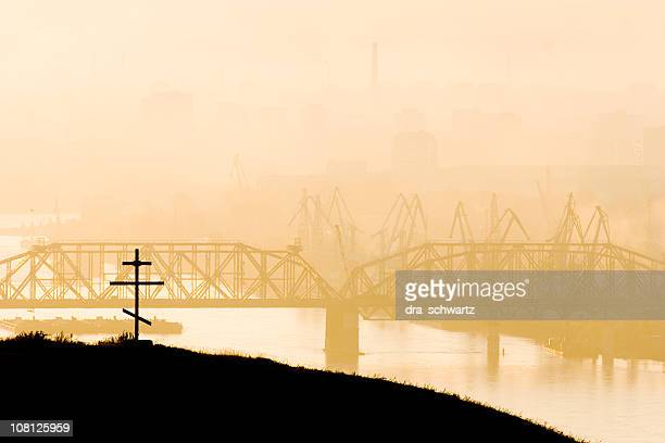 Silhouette of Bridge Over River and Orthodox Cross on Hill