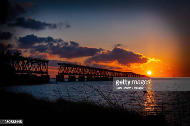 silhouette of bridge over sea against sky during sunset, bahia honda state park, united states - florida us state stock pictures, royalty-free photos & images