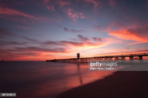 silhouette of bridge over sea during sunset - seal beach stock pictures, royalty-free photos & images