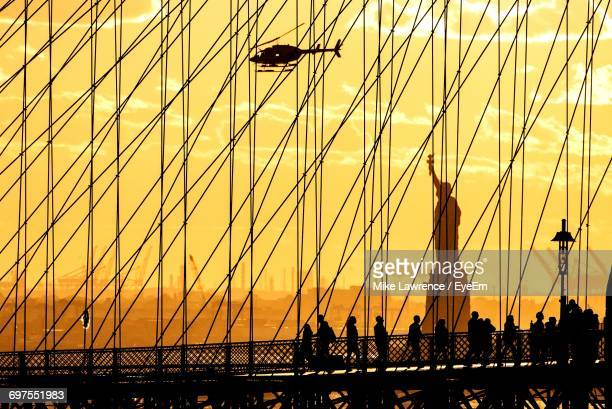 Silhouette Of Brooklyn Bridge Against Statue Of Liberty At Sunset