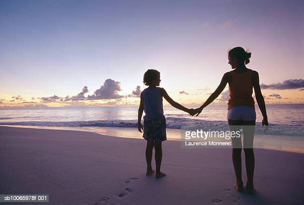 Silhouette of brother and sister (8-14) standing on beach, rear view
