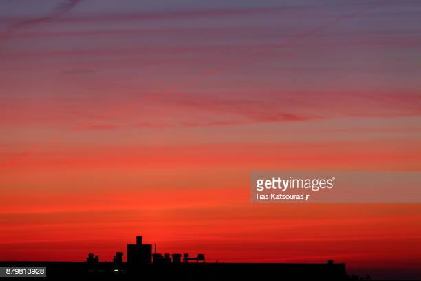 Silhouette of building at dawn, against blood red sky