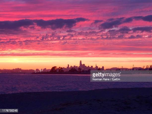 silhouette of buildings against cloudy sky at sunset - magenta stock pictures, royalty-free photos & images