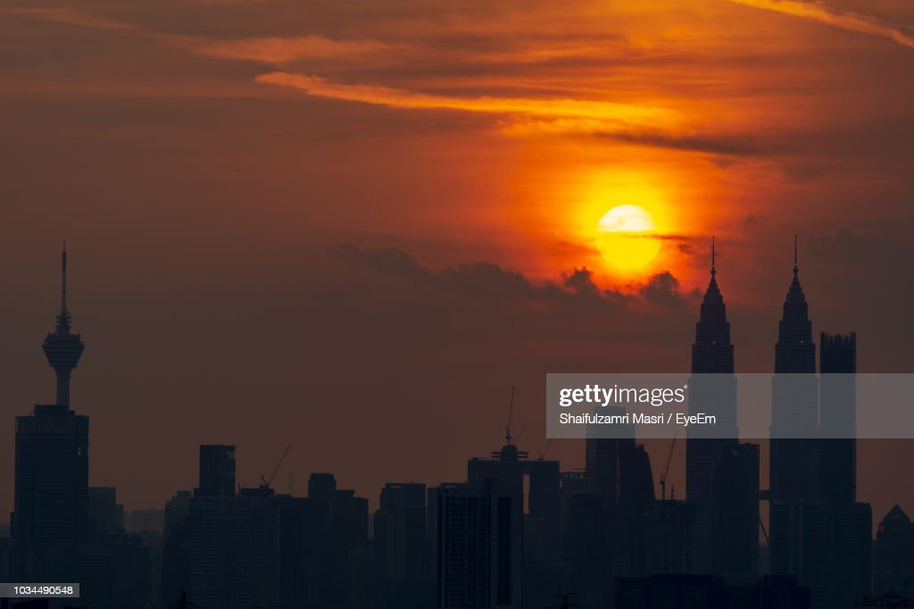 Silhouette Of Buildings Against Cloudy Sky During Sunset : Stock Photo