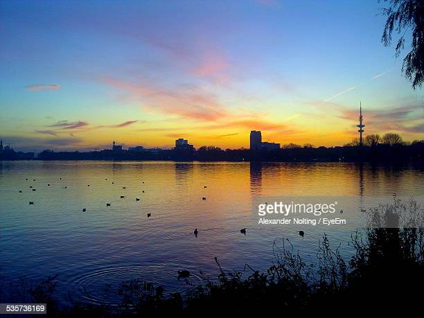 Silhouette Of Buildings At Sunset, Lake In Foreground