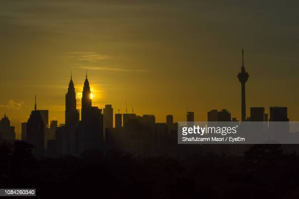Silhouette Of Buildings In City During Sunrise