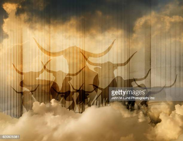 Silhouette of bulls and pillars in cloudy sky