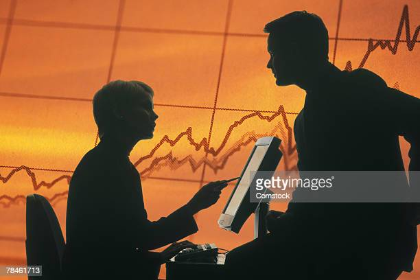 Silhouette of business people at computer with chart