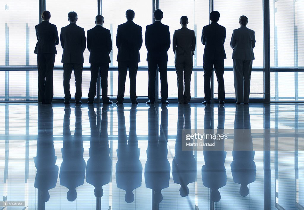Silhouette of business people in a row looking out lobby window : Stock Photo