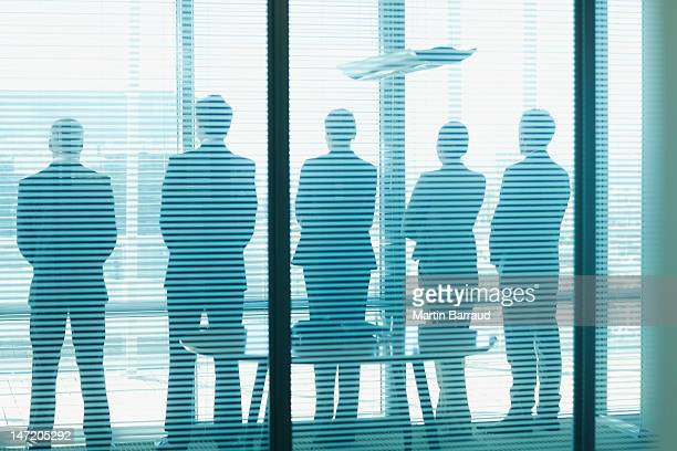 silhouette of business people in a row looking out office window - five people stock pictures, royalty-free photos & images