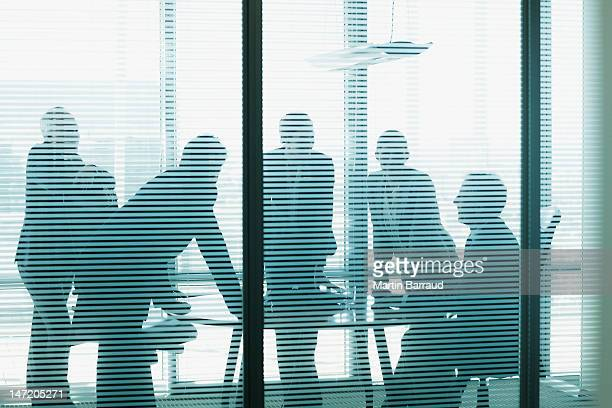 silhouette of business people leaning on table in conference room - five people stock pictures, royalty-free photos & images