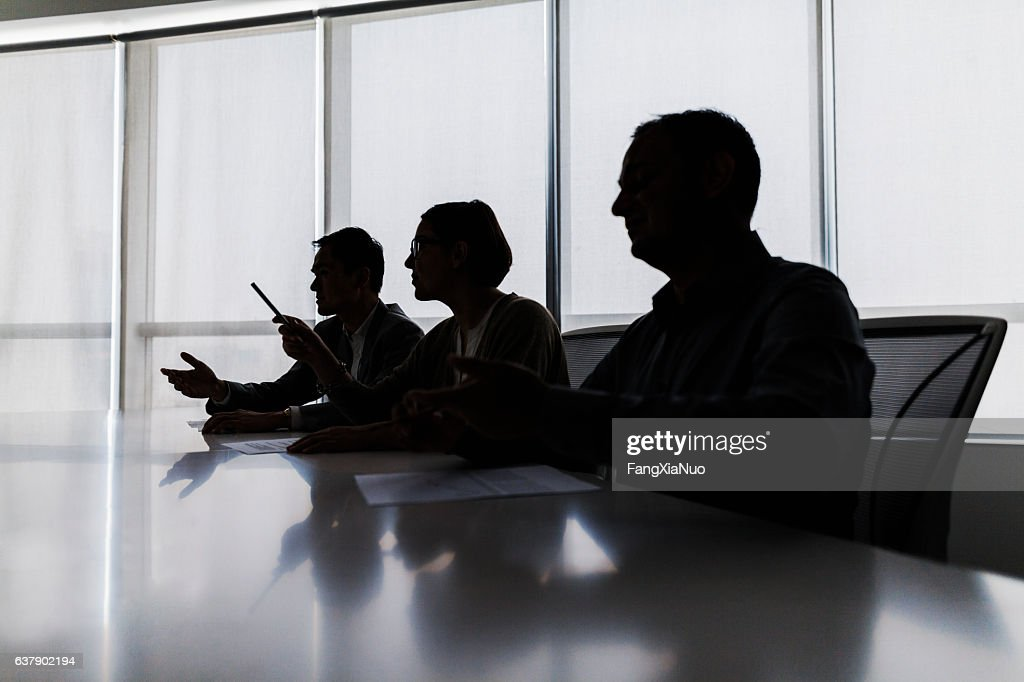 Silhouette of business people negotiating at meeting table : Stock Photo