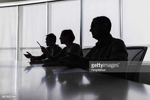 silhouette of business people negotiating at meeting table - authority stock pictures, royalty-free photos & images