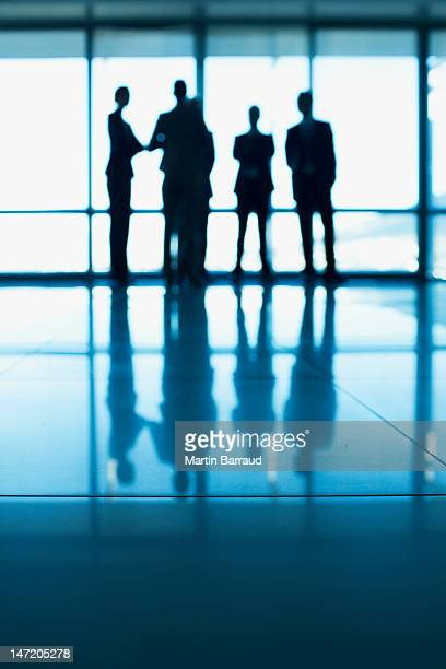 Silhouette of business people standing at lobby window