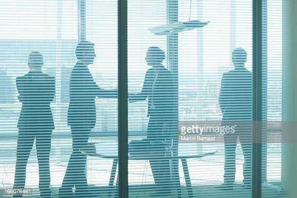 silhouette of business people talking in conference room - persuasion stock pictures, royalty-free photos & images