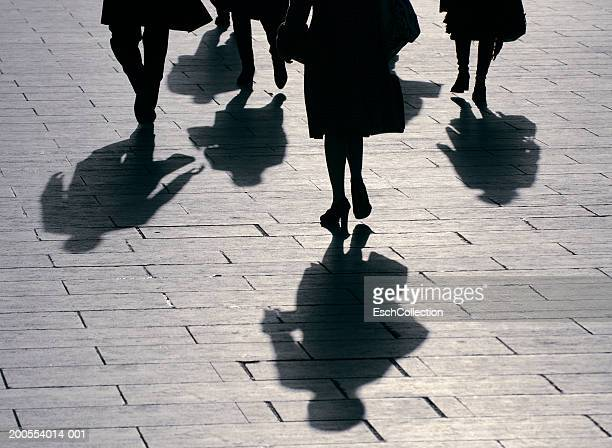 Silhouette of business people walking, low section