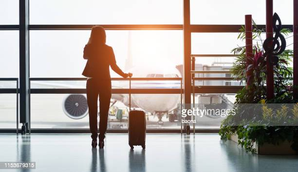 silhouette of business traveler makes a call while waiting for her flight - business travel stock pictures, royalty-free photos & images