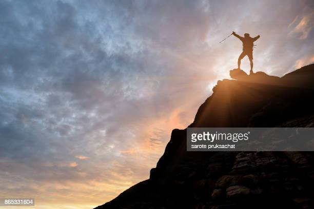 silhouette of businessman hike on the peak of rocks mountain at sunset, success, winner, leader concept