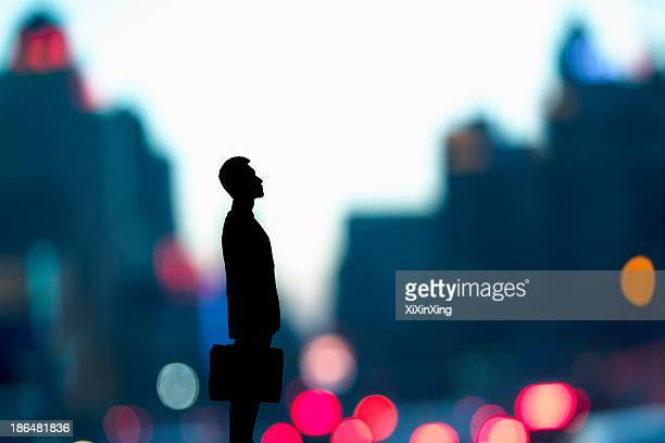 Silhouette of businessman holding a briefcase with blurred city lights behind him