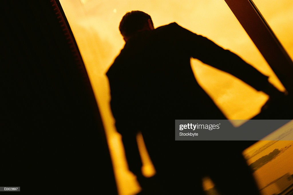 Silhouette of businessman in front of high-rise window : Stock Photo