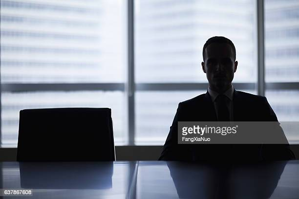 silhouette of businessman in office meeting room - negative emotion stock pictures, royalty-free photos & images