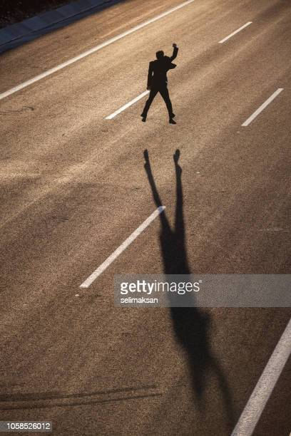 Silhouette Of Businessman In Suit Jumping On Highway