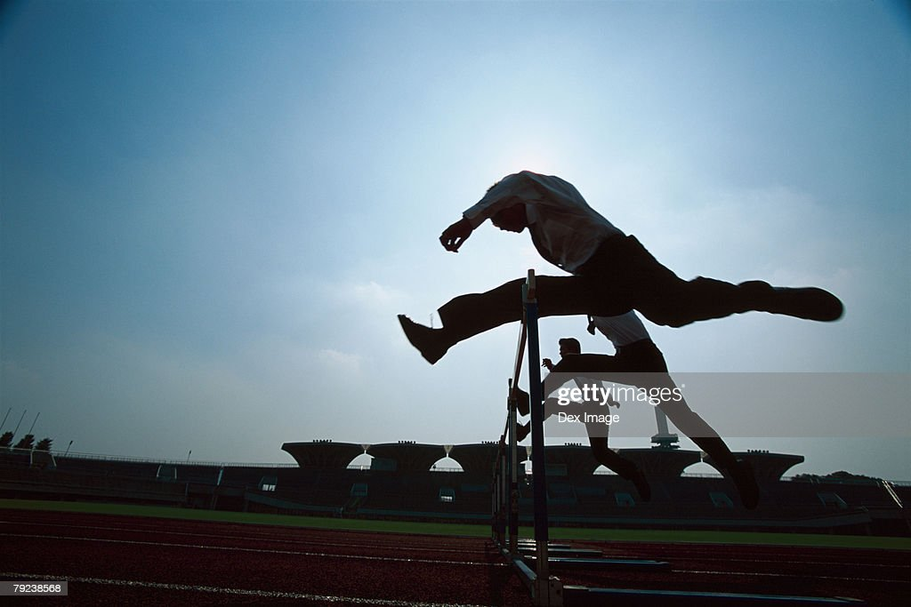 Silhouette of businessman leaping hurdle : Stock Photo