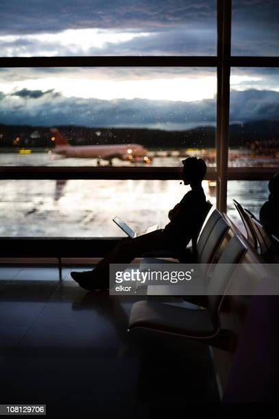 Silhouette of Businessman Sitting in Airport Terminal