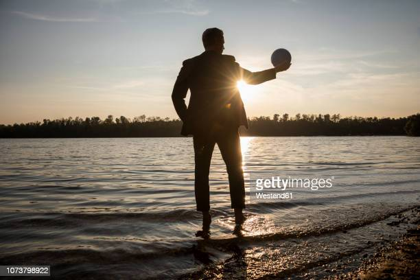 silhouette of businessman standing at lakeshore by sunset looking at ball in his hand - seeufer stock-fotos und bilder