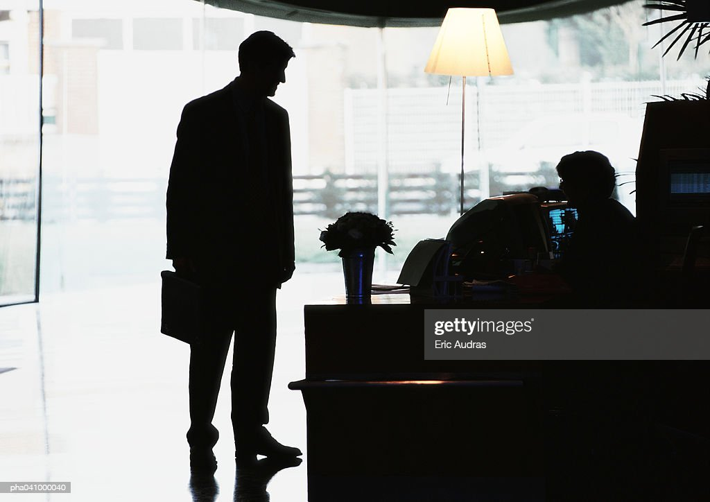 Silhouette of businessman standing in front of desk : Photo