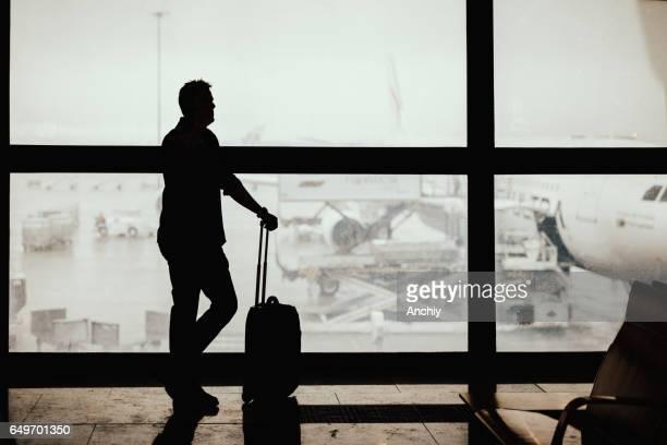 Silhouette der Geschäftsmann seinen Flug warten