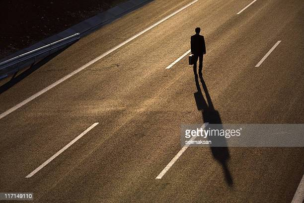 Silhouette Of Businessman Walking In The Middle Of Highway