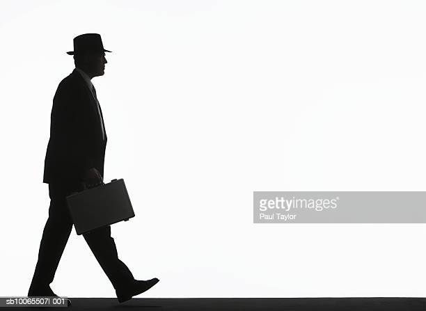 Silhouette of businessman walking with briefcase, side view