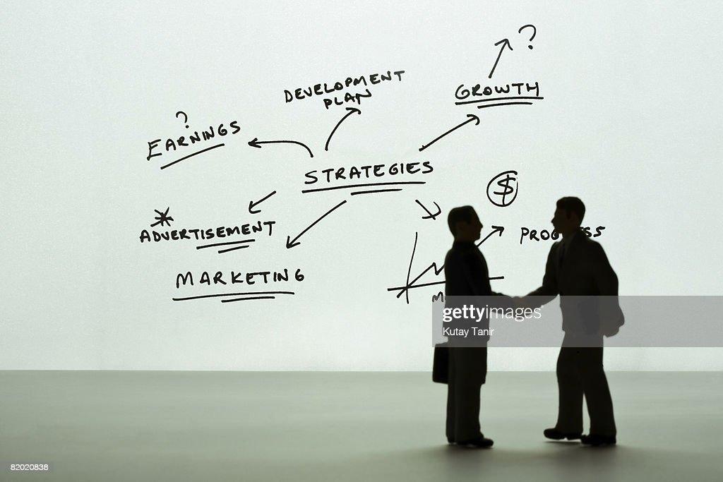 Silhouette of businessmen figurines shaking hands, diagram in background. (Focus on background) : Bildbanksbilder